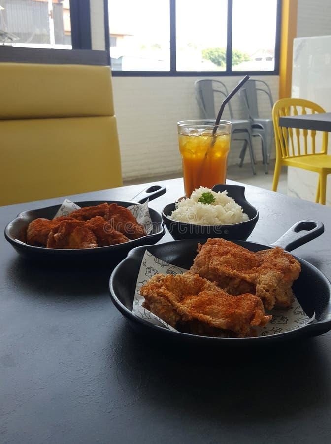 Spicy fried chicken set serving on black pan and white paper on. Spicy fried chicken set serving on black pan and white paper with sticky rice and lemon tea on stock photos