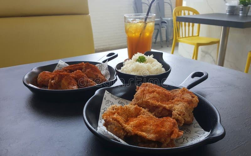 Spicy fried chicken set serving on black pan and white paper on. Spicy fried chicken set serving on black pan and white paper with sticky rice and lemon tea on stock photo