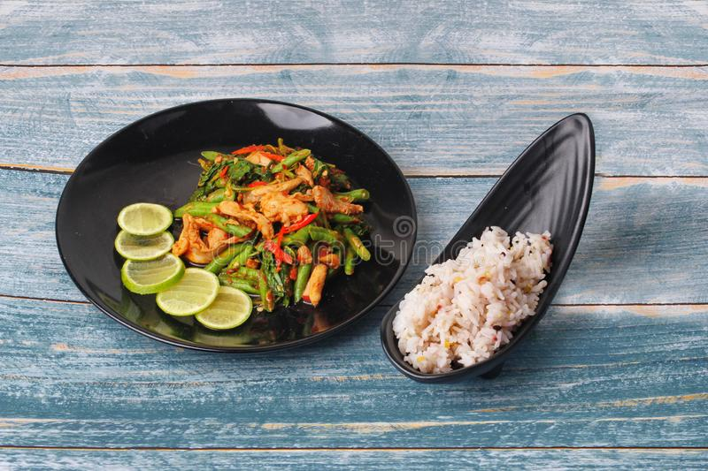 Spicy fried cowpea and basil with pork topped sliced green lemon served with japanese seed for rice in jasmine rice on black royalty free stock image