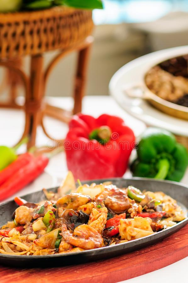 Spicy fried seafood on a hot pan. Smoke to taste. And beautifully decorated royalty free stock images