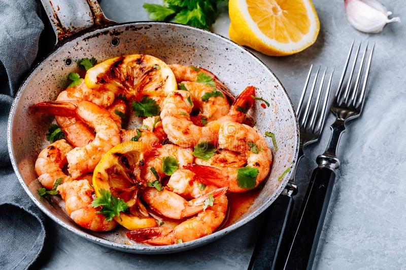 Spicy garlic chilli Shrimps on frying pan with lemon and cilantro royalty free stock photography