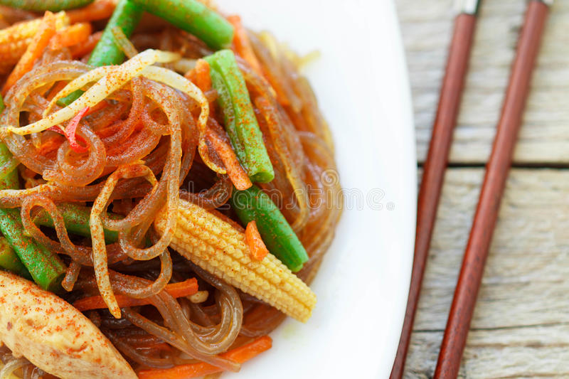 Spicy glass noodles with chicken, green beans, carrots, corn and soy sprouts. Oriental cuisine royalty free stock image