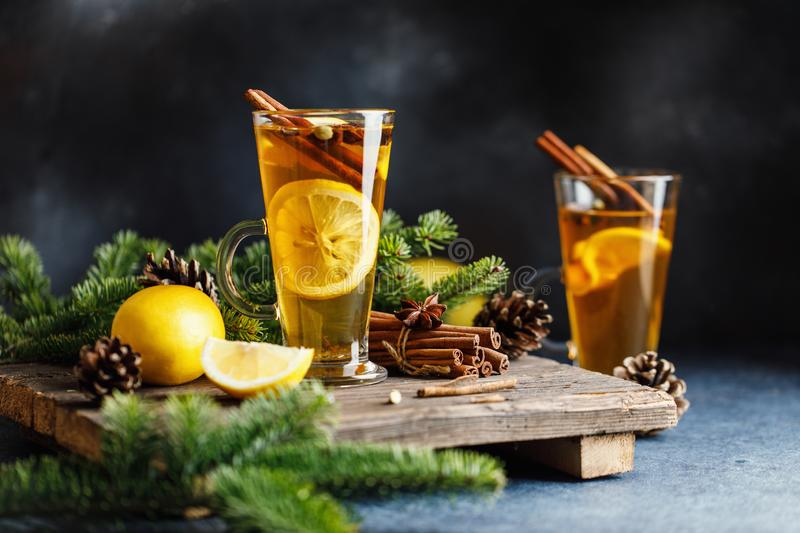 Spicy grog cocktail. Christmas or New Year hot winter drink. Autumn and winter cocktail - grog, hot sangria, mulled wine with tea,. Lemon, rome, cinnamon, anise stock photos