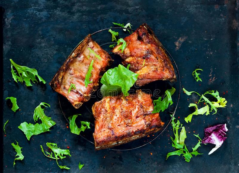 Spicy hot grilled spare ribs from BBQ served with arugula on vintage rusty metal background. Banner. Top view, copy spacen stock photo