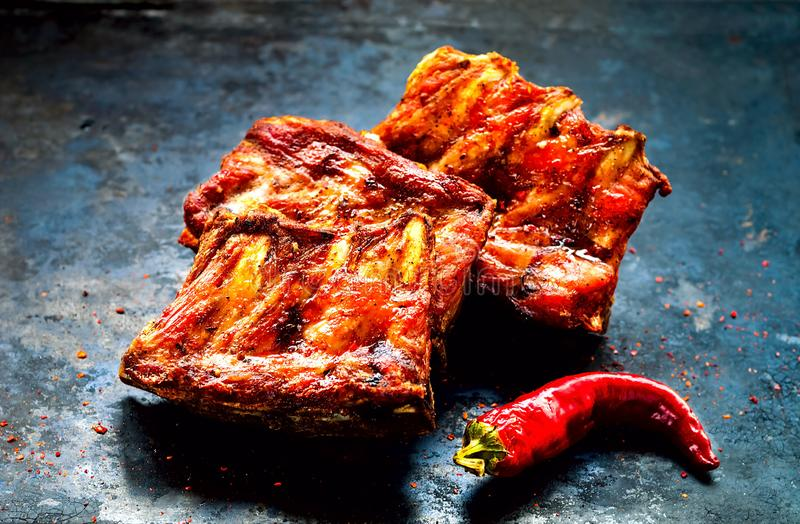 Spicy hot grilled spare ribs from BBQ served with hot chili pepper on vintage rusty metal background. Banner.Top view,copy spacen royalty free stock images