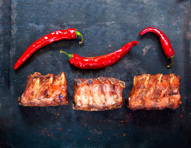 Spicy hot grilled spare ribs from BBQ served with hot chili pepper on vintage rusty metal background. Banner.Top viewn stock photography