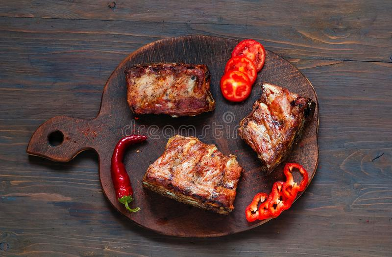 Spicy hot grilled spare ribs from BBQ served with hot chili pepper and lime on dark wooden background. Banner. Top view, stock photos