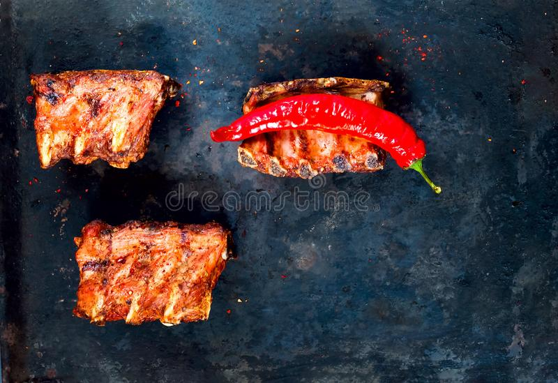 Spicy hot grilled spare ribs from BBQ served with hot chili pepper on vintage rusty metal background. n royalty free stock images