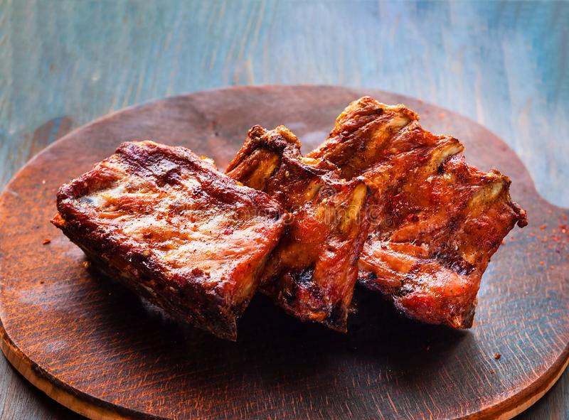 Spicy hot grilled spare ribs from BBQ served on wooden board royalty free stock photo