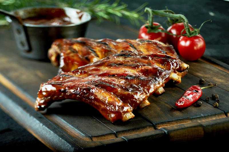 Spicy hot grilled spare ribs from a summer BBQ. Served with a hot chili pepper and fresh tomatoes on an old vintage wooden cutting board stock image