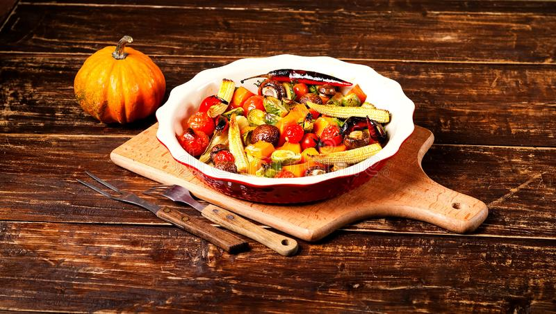 Spicy hot vegetables, cooked on an grill in ceramic bowl on wooden background. The concept of healthy eating and delicious food. Top view, copy space, closeup stock image