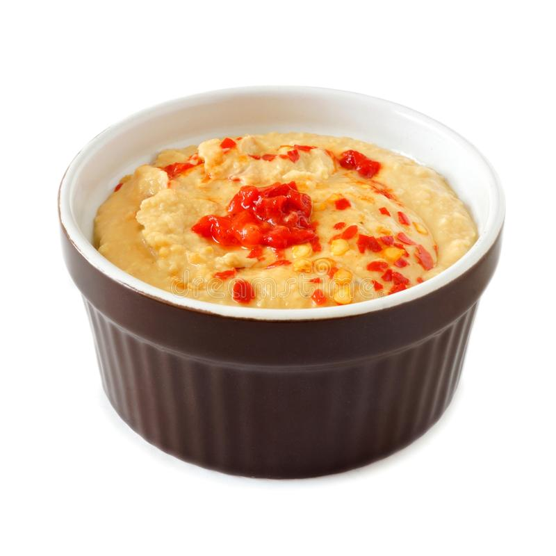 Spicy hummus with hot peppers in ramekin bowl over white royalty free stock photo