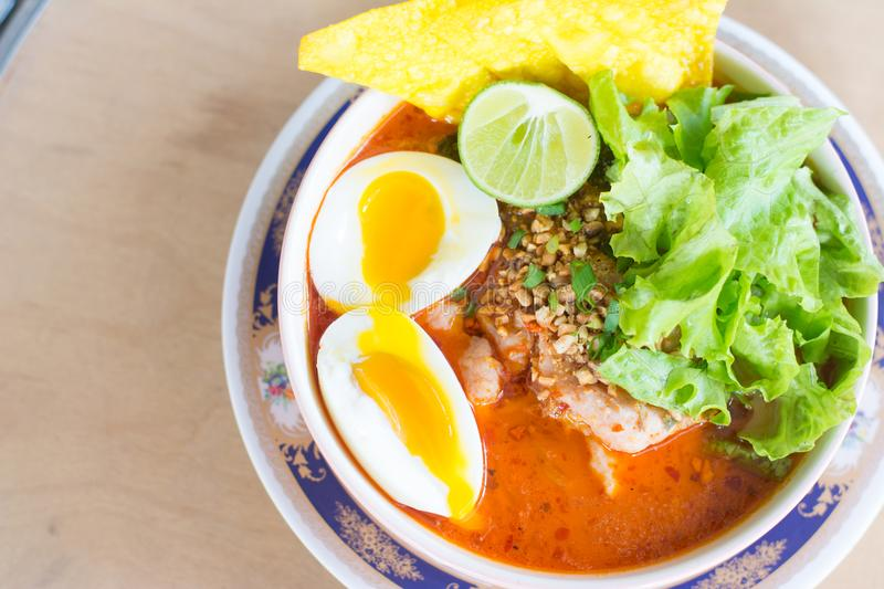 Spicy lemongrass flavored flat noodles with pork and medium boil egg stock photo