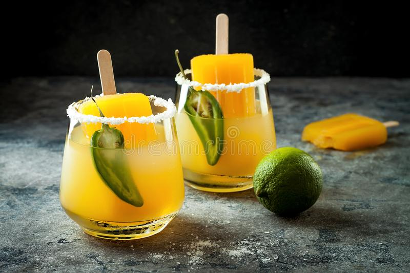 Spicy mango popsicle margarita cocktail with jalapeno and lime. Mexican alcoholic drink for Cinco de mayo party. Spicy mango popsicle margarita cocktail with royalty free stock image