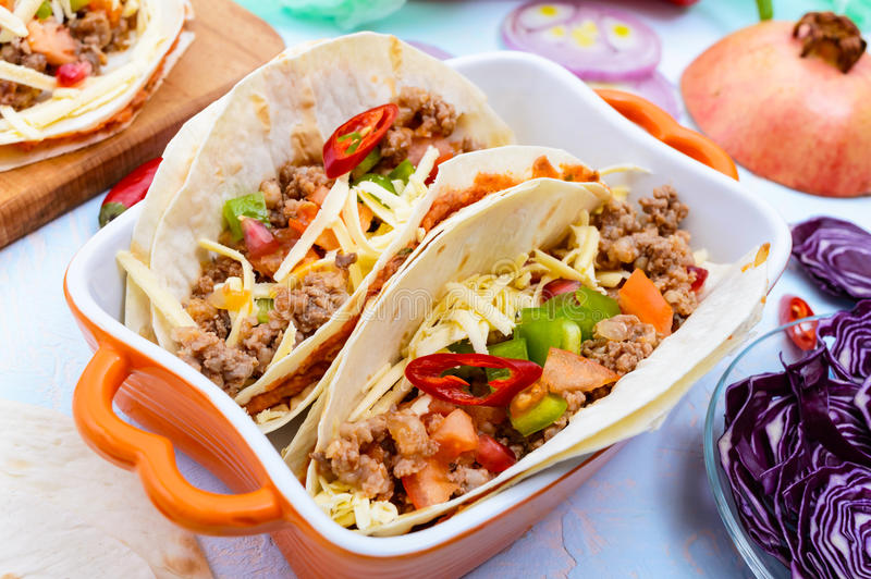 Spicy Mexican tacos with minced meat, mashed beans, vegetables, grated cheese royalty free stock photography