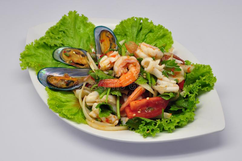 Spicy mixed seafood salad Yum Talay on white plate royalty free stock photos