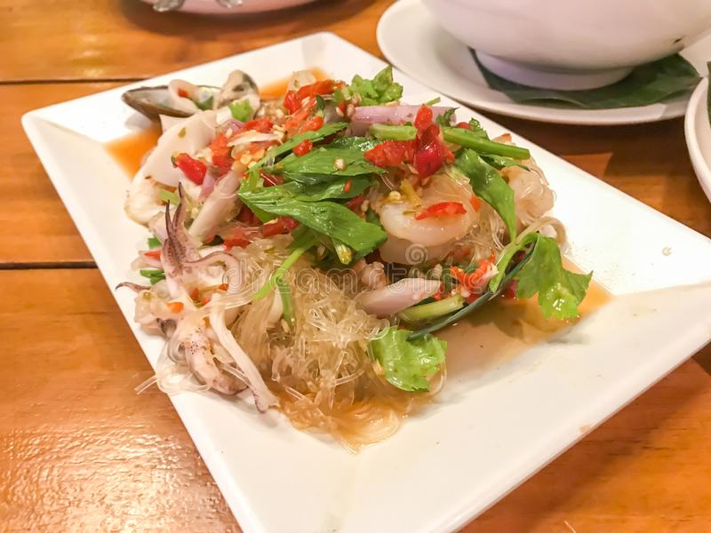 Spicy Mung Bean Noodle and seafood salad on wood table in restaurant.Spicy and delicious Thai food royalty free stock photos
