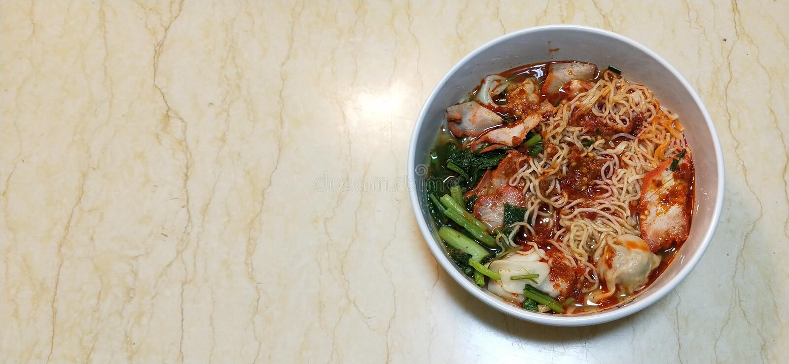 Spicy noodle with dumpling and roasted red pork. On marble table royalty free stock photos