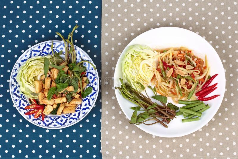 Spicy papaya salad and Spicy sour mixed herb salad with fried to. Fu for Chinese vegetable festival stock photo