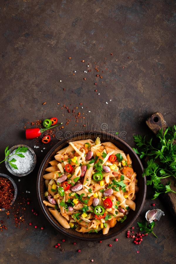 Spicy pasta penne bolognese with vegetables, beans, chili and cheese in tomato sauce stock photography