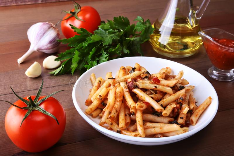 Spicy penne pasta bolognese with vegetables, chili and cheese in tomato sauce on the background of tomatoes, garlic stock images