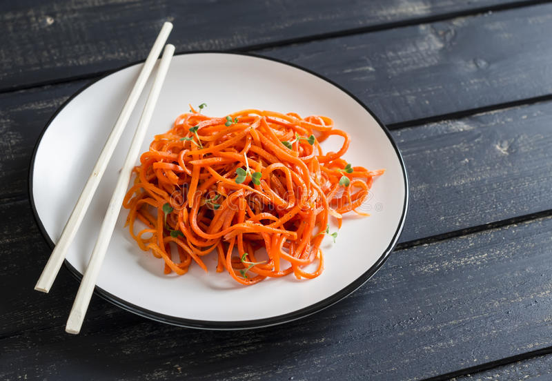 Spicy pickled carrot salad in an asian style on a white plate on a dark wooden background. Vegan food royalty free stock photos