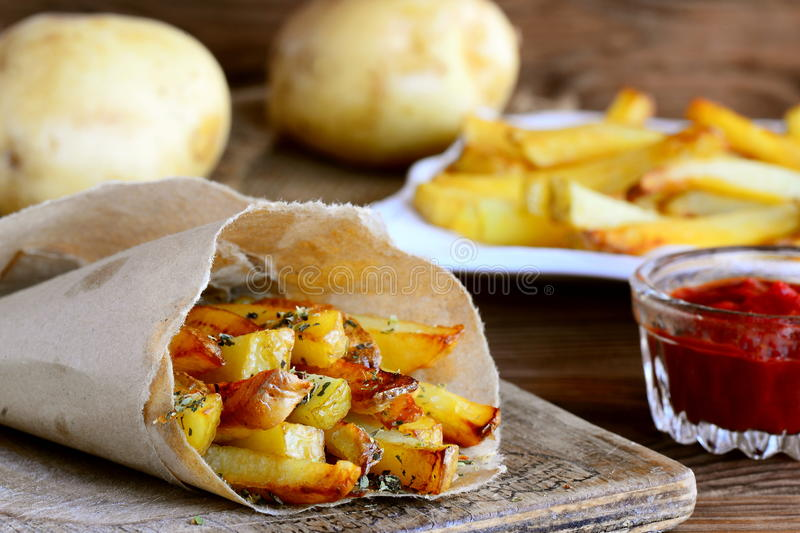 Spicy potato fries. Baked sweet potato fries in paper and white plate, spicy tomato sauce, raw potato on a wooden table. Closeup royalty free stock photo