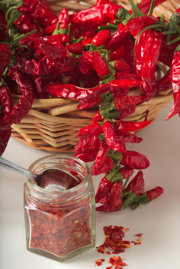 Spicy red pepper ground in the glass jar, with healthy dried peppers in the basket. On White background royalty free stock image