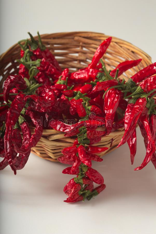 Spicy red pepper ground in the glass jar, with healthy dried peppers in the basket. On White background stock images