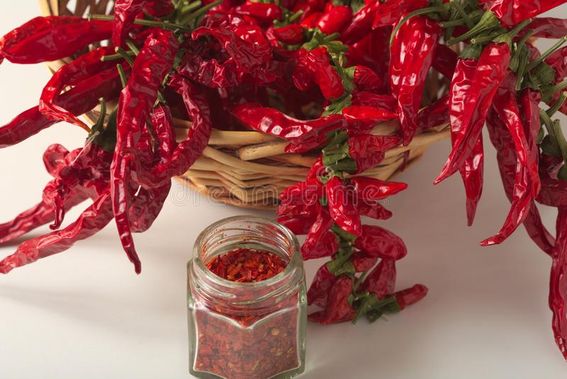 Spicy red pepper ground in the glass jar, with healthy dried peppers in the basket. On White background stock photos