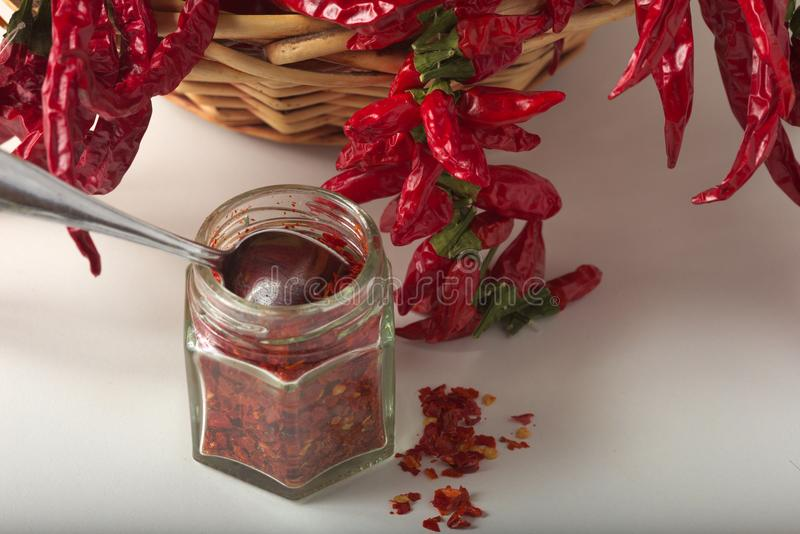 Spicy red pepper ground in the glass jar, with healthy dried peppers in the basket. On White background stock photography