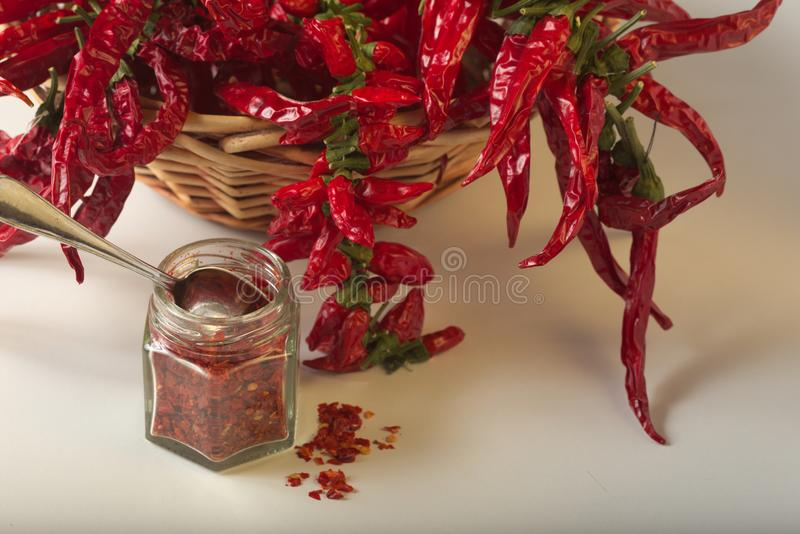 Spicy red pepper ground in the glass jar, with healthy dried peppers in the basket. On White background stock photo
