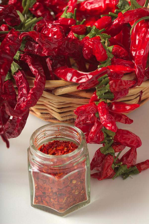 Spicy red pepper ground in the glass jar, with healthy dried peppers in the basket royalty free stock image