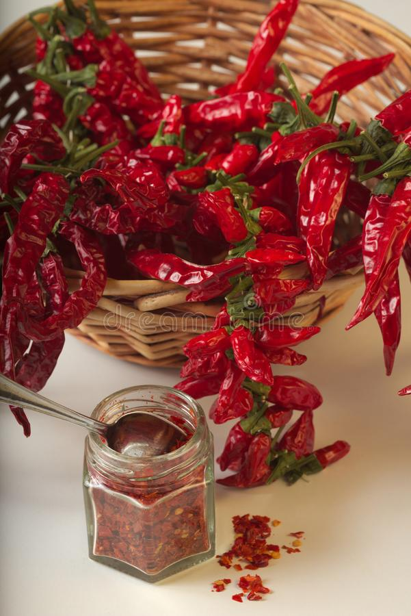 Spicy red pepper ground in the glass jar, with healthy dried peppers in the basket. On White background royalty free stock photos