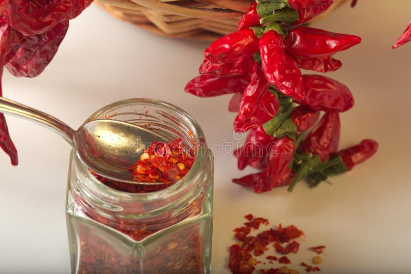 Spicy red pepper ground in the glass jar, with healthy dried peppers in the basket royalty free stock photo