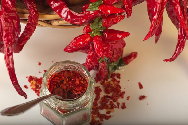 Spicy red pepper ground in the glass jar, with healthy dried peppers in the basket stock image