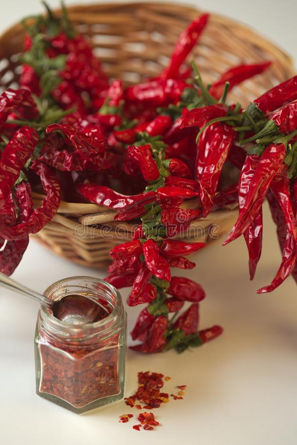 Spicy red pepper ground in the glass jar, with healthy dried peppers in the basket stock photos