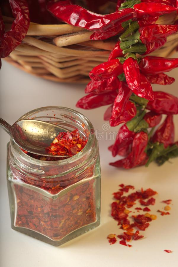 Spicy red pepper ground in the glass jar, with healthy dried peppers in the basket stock photo