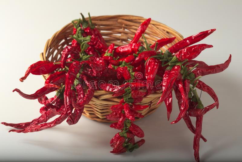Spicy red pepper ground, with healthy dried peppers in the basket. On White background stock images