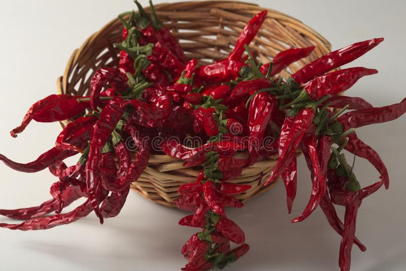 Spicy red pepper ground, with healthy dried peppers in the basket. On White background stock photography