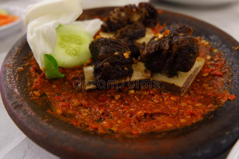 Spicy ribs as traditional and delicious Indonesian food. Traditional Food Spicy Ribs of Cow and called Iga Penyet in Indonesian language - very tasty and spicy royalty free stock photos