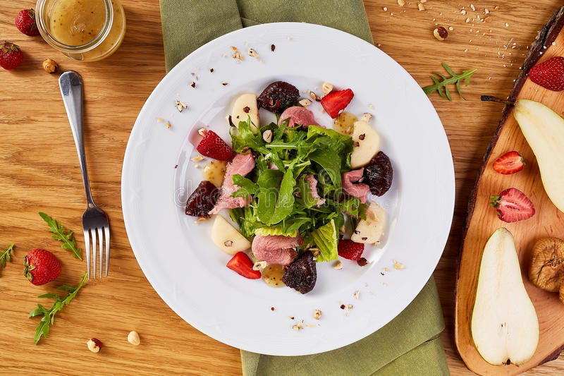Spicy salad with beef and sun-dried tomatoes. Salad with pear, mushrooms, strawberries and greens. stock photos