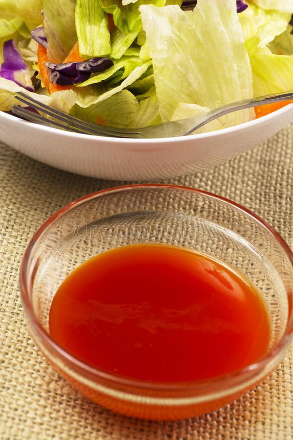 Spicy Salad Dressing. Spicy red salad dressing on the side.  Iceberg salad in background stock photo