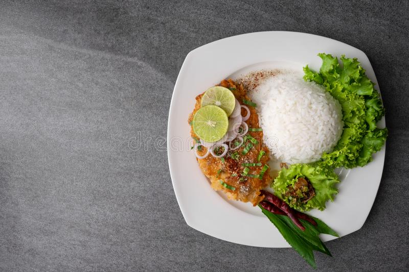 Spicy salad with fried chicken and rice in white dish on table royalty free stock images