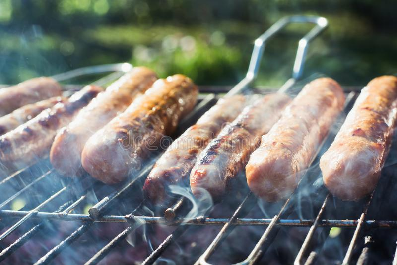 Tasty sausages grilling on portable barbecue on summer picnic. Outdoors. Smoke and fire. Close up. Spicy sausages grilling on portable barbecue on summer picnic stock photo