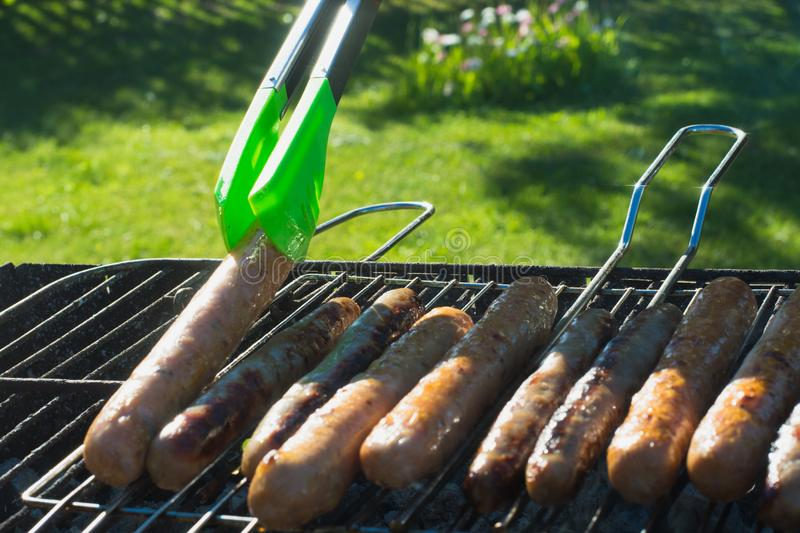 Spicy sausages grilling on portable barbecue on summer picnic. Outdoors. Smoke and fire. Close up. Tasty sausages grilling on portable barbecue on summer picnic stock photography