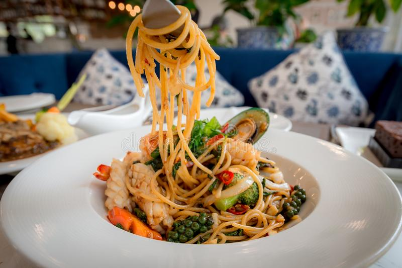 Spicy Seafood Spaghetti stir fried Pad Cha rolled in the fork on white dish of luxury restaurant. Thai Signature Food royalty free stock photos