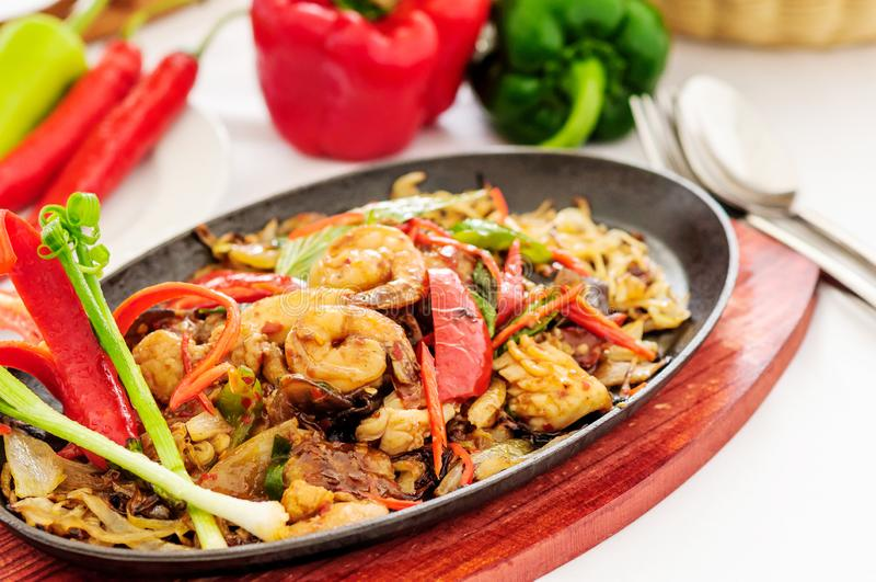 Spicy fried seafood on a hot pan. Spicy seafood stir-fried on a hot pan .. Bright colors and beautifully decorated royalty free stock photography