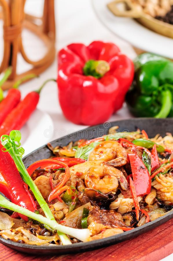 Spicy fried seafood on a hot pan. Spicy seafood stir-fried on a hot pan .. Bright colors and beautifully decorated stock photo