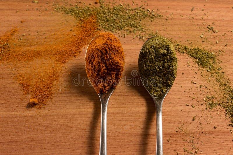 Spicy seasonings on metal spoons royalty free stock photos